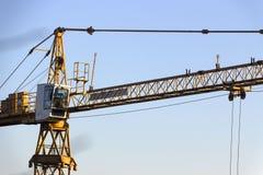 反对蓝天的黄色工业建筑用起重机 库存照片