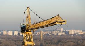 反对蓝天的黄色工业建筑用起重机 免版税库存图片