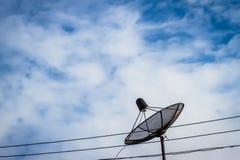 反对蓝天的黑卫星盘 免版税库存照片