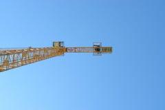 反对蓝天的黄色塔吊在建造场所 免版税库存照片
