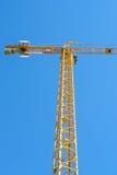 反对蓝天的黄色塔吊在建造场所 库存图片