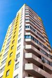 反对蓝天背景的新的高公寓 免版税库存图片