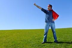 反对蓝天背景的超级英雄父亲 免版税库存图片