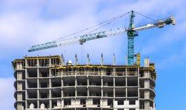 反对蓝天,修建一个多层的大厦的过程的塔吊 库存图片