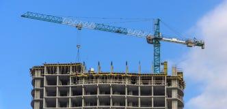 反对蓝天,修建一个多层的大厦的过程的塔吊 库存照片