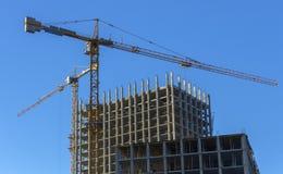 反对蓝天,修建一个多层的大厦的过程的塔吊 图库摄影