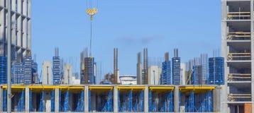 反对蓝天,修建一个多层的大厦的过程的塔吊 免版税图库摄影