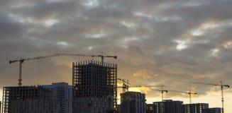 反对蓝天,修建一个多层的大厦的过程的塔吊 免版税库存图片