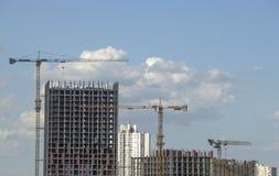 反对蓝天,修建一个多层的大厦的过程的塔吊 免版税库存照片