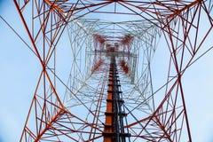 反对蓝天-底视图的红色白色电信塔 免版税库存照片