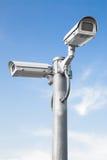 反对蓝天-选择聚焦的两部安全监控相机 免版税库存照片