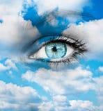 反对蓝色云彩的美丽的蓝眼睛-精神概念 免版税库存图片