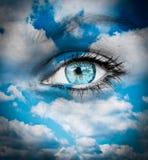反对蓝色云彩的美丽的蓝眼睛-精神概念 免版税图库摄影