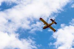 反对蓝色和多云天空的消防队员航空器 免版税库存照片