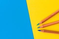反对蓝色和黄色背景的三支铅笔 图库摄影