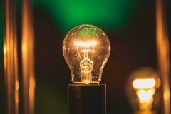 反对蓝色墙壁背景的发光的电灯泡 免版税库存图片