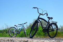 反对蓝色夏天天空的两辆自行车 库存照片