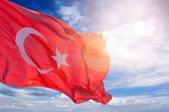 反对蓝色多云天空的土耳其旗子 土耳其的旗子在阳光和强光下 图库摄影
