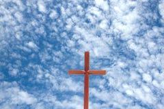 反对蓝色多云天空背景的木十字架 库存照片