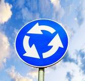 反对蓝色多云的蓝色环形交通枢纽交叉路公路交通标志 免版税库存照片
