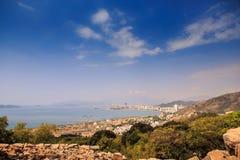 反对蓝色海明亮的天空云彩的岩石青山 图库摄影