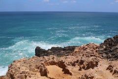 反对蓝色海洋和天空的红色石峭壁在海角布里奇沃特,澳大利亚 库存照片