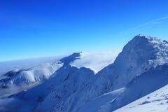 反对蓝色的美丽的积雪覆盖的山 库存照片