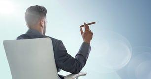 反对蓝色背景和火光的供以座位的商人抽烟的雪茄 免版税库存照片