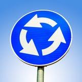 反对蓝色背景的蓝色环形交通枢纽交叉路公路交通标志 免版税库存图片