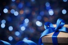 反对蓝色bokeh背景的礼物盒或礼物和圣诞节球 不可思议的假日贺卡 免版税库存照片