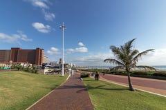 反对蓝色Coudy都市风景的海滩前的散步在德班 免版税库存照片