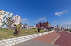 反对蓝色Coudy都市风景的海滩前的散步在德班 库存图片