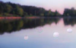 反对被弄脏的自然背景的肥皂泡 免版税库存图片