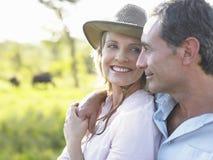 反对被弄脏的草甸的愉快的夫妇 免版税库存照片