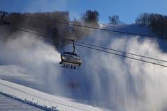 反对被雾化的人为雪的滑雪电缆车 免版税图库摄影