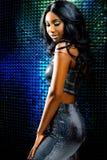 反对迪斯科背景的可爱的非洲妇女 免版税图库摄影