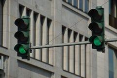 反对都市城市背景的两个绿色红绿灯 免版税库存照片