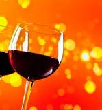反对金黄bokeh的两块红葡萄酒玻璃点燃背景 库存图片