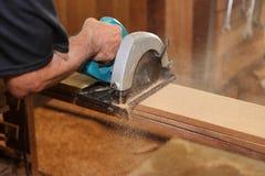 反对锯木屑的电圆锯用资深木匠的人工使用在木匠业woodshop 图库摄影