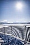 反对随风飘飞的雪的篱芭 库存图片