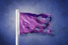 反对难看的东西背景的被撕毁的紫色旗子飞行 免版税库存照片
