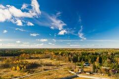 反对风景cloudscape的五颜六色的秋天森林 库存图片