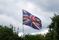 反对风雨如磐的天空的被打击的英国国旗旗子 库存照片