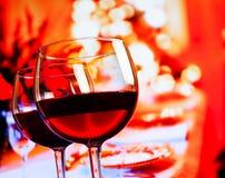 反对餐馆桌背景的两块红葡萄酒玻璃 库存照片