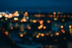 反对黑暗的晚上天空的被弄脏的城市光 库存照片