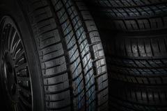 反对黑暗的背景的新和未使用的车胎 库存照片