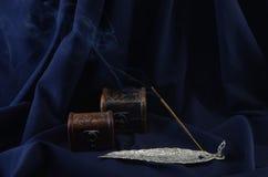 反对黑暗的背景的燃烧的香火棍子 免版税库存照片