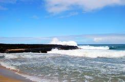 反对黑熔岩的碎波在考艾岛 免版税库存图片