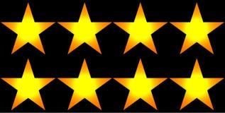 反对黑背景的发光的黄色星 免版税图库摄影