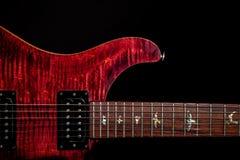 反对黑背景的美丽的红色电吉他 库存图片